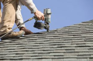Man working on roof with nail gun. Staunton Roofing 540-255-0068