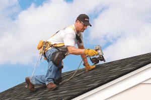 Worker repairing hail damage on shingle home in Staunton, Virginia - Staunton Roofing